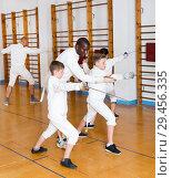 Купить «Fencing instructor with young fencers in training room», фото № 29456335, снято 30 мая 2018 г. (c) Яков Филимонов / Фотобанк Лори