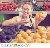 Купить «Cheerful female seller wearing apron holding plums», фото № 29456651, снято 18 июля 2019 г. (c) Яков Филимонов / Фотобанк Лори