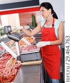 Купить «Female seller weighing sausages in shop», фото № 29464763, снято 22 июня 2018 г. (c) Яков Филимонов / Фотобанк Лори