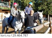 Купить «Positive mature couple with jockey learn to riding horse at farm», фото № 29464787, снято 4 июля 2018 г. (c) Яков Филимонов / Фотобанк Лори