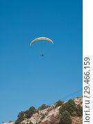 Купить «Paraglider is flying in the blue sky. Paragliding in the sky on a sunny day.», фото № 29466159, снято 4 сентября 2018 г. (c) Евгений Глазунов / Фотобанк Лори