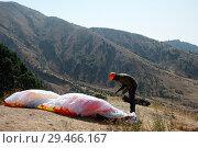 Купить «Man paraglider taking off from the edge of the mountain. Paragliding sports», фото № 29466167, снято 4 сентября 2018 г. (c) Евгений Глазунов / Фотобанк Лори