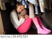 Купить «Грустная маленькая девочка прячется в шкафу», фото № 29470551, снято 6 октября 2018 г. (c) Лариса Капусткина / Фотобанк Лори