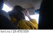 Купить «Young woman sits on the driver's seat, puts down the visor and looks in the mirror», видеоролик № 29470559, снято 22 февраля 2020 г. (c) Константин Шишкин / Фотобанк Лори