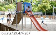 Купить «Cheerful boy and girl play games and running around sliding toy in park», видеоролик № 29474267, снято 23 июля 2018 г. (c) Яков Филимонов / Фотобанк Лори