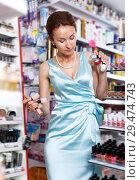 Купить «Cheerful woman choosing new nail polishes», фото № 29474743, снято 21 июня 2018 г. (c) Яков Филимонов / Фотобанк Лори