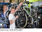 Купить «Professional man checking tire on cycle wheel», фото № 29475087, снято 17 июля 2017 г. (c) Яков Филимонов / Фотобанк Лори
