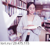 Купить «girl browsing textbooks in bookstore», фото № 29475115, снято 18 января 2018 г. (c) Яков Филимонов / Фотобанк Лори
