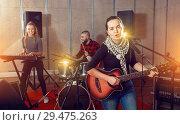 Купить «Attractive female soloist playing guitar and singing with her mu», фото № 29475263, снято 26 октября 2018 г. (c) Яков Филимонов / Фотобанк Лори