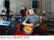 Купить «Attractive female soloist playing guitar and singing with her music band in sound studio», фото № 29475275, снято 26 октября 2018 г. (c) Яков Филимонов / Фотобанк Лори