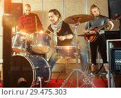Купить «Passionate emotional female drummer with her bandmates practicin», фото № 29475303, снято 26 октября 2018 г. (c) Яков Филимонов / Фотобанк Лори