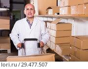 Купить «Portrait of mature man standing with cart», фото № 29477507, снято 22 апреля 2017 г. (c) Яков Филимонов / Фотобанк Лори