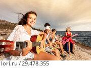 Купить «Girl playing guitar with her friends on the beach», фото № 29478355, снято 22 июля 2018 г. (c) Сергей Новиков / Фотобанк Лори