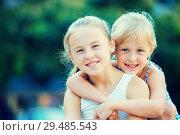 Купить «Two small happy sisters outdoors», фото № 29485543, снято 20 июля 2017 г. (c) Яков Филимонов / Фотобанк Лори