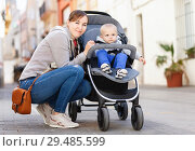 Купить «Female and her toddler are standing on the street after shopping in time walking.», фото № 29485599, снято 18 апреля 2018 г. (c) Яков Филимонов / Фотобанк Лори