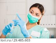 Купить «Female nurse in mask holding syringe for injection in hospital», фото № 29485603, снято 1 мая 2018 г. (c) Яков Филимонов / Фотобанк Лори