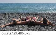 Купить «People lie on the beach. a woman with two children lies on the stones. the waves break on the pebble beach.», видеоролик № 29486075, снято 25 марта 2019 г. (c) Константин Мерцалов / Фотобанк Лори