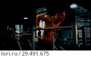 Купить «man doing triceps dip exercise on bars in dark gym», видеоролик № 29491675, снято 22 марта 2019 г. (c) Syda Productions / Фотобанк Лори