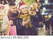 Купить «young couple in Christmas hat buying decoration at fair», фото № 29492235, снято 14 декабря 2017 г. (c) Яков Филимонов / Фотобанк Лори