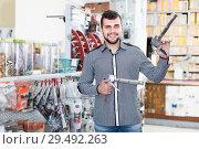 Купить «Male deciding on glue gun in houseware shop», фото № 29492263, снято 5 апреля 2017 г. (c) Яков Филимонов / Фотобанк Лори