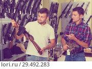 Купить «Friends choosing air-powered gun», фото № 29492283, снято 4 июля 2017 г. (c) Яков Филимонов / Фотобанк Лори