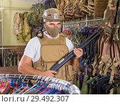 Купить «adult guy in military equipment with weapon in army shop», фото № 29492307, снято 4 июля 2017 г. (c) Яков Филимонов / Фотобанк Лори