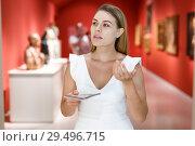 Купить «Woman observing museum exposition», фото № 29496715, снято 28 июля 2018 г. (c) Яков Филимонов / Фотобанк Лори