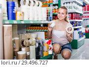 Купить «smiling woman customer choosing adhesive tape in household store», фото № 29496727, снято 9 декабря 2018 г. (c) Яков Филимонов / Фотобанк Лори
