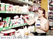 smiling young woman customer choosing paint medium in bottle in hypermarket. Стоковое фото, фотограф Яков Филимонов / Фотобанк Лори