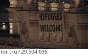 Купить «Refugees Welcome banner on Cybele Palace in Madrid, Spain», видеоролик № 29504035, снято 17 января 2018 г. (c) Данил Руденко / Фотобанк Лори