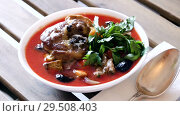 Spicy tomato soup with lamb, prunes and dried apricots served in white bowl with greens. Стоковое видео, видеограф Яков Филимонов / Фотобанк Лори