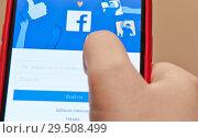 Купить «Вход в мобильную версию Facebook. Телефон в руке», фото № 29508499, снято 1 декабря 2018 г. (c) E. O. / Фотобанк Лори