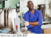 Купить «Confident African American glazier working with glass on stationary drilling machine», фото № 29509447, снято 16 мая 2018 г. (c) Яков Филимонов / Фотобанк Лори