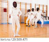 Купить «Young female in mask with foil at fencing workout», фото № 29509471, снято 11 июля 2018 г. (c) Яков Филимонов / Фотобанк Лори