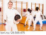 Купить «Smiling young female in uniform standing at fencing room», фото № 29509475, снято 11 июля 2018 г. (c) Яков Филимонов / Фотобанк Лори