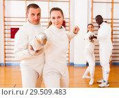 Купить «Woman practicing new movements with trainer at fencing room», фото № 29509483, снято 11 июля 2018 г. (c) Яков Филимонов / Фотобанк Лори