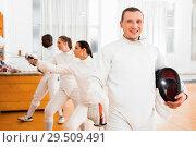 Купить «Active young male fencer in uniform standing with mask and foil at fencing room», фото № 29509491, снято 11 июля 2018 г. (c) Яков Филимонов / Фотобанк Лори