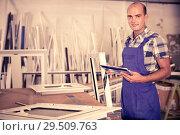 Купить «Focused workman in overalls controlling quality of assembly of plastic window in workshop», фото № 29509763, снято 19 июля 2017 г. (c) Яков Филимонов / Фотобанк Лори