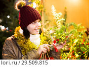 Купить «Portrait of female teenage customer choosing floral decorations», фото № 29509815, снято 12 декабря 2016 г. (c) Яков Филимонов / Фотобанк Лори