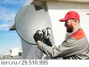 Купить «Service worker installing and fitting satellite antenna dish for cable TV», фото № 29510995, снято 15 октября 2018 г. (c) Дмитрий Калиновский / Фотобанк Лори