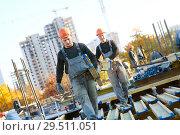 Купить «construction workers at building area installing wormwork», фото № 29511051, снято 12 октября 2018 г. (c) Дмитрий Калиновский / Фотобанк Лори