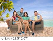 Купить «friends sitting on sofa over tropical beach», фото № 29512071, снято 30 июня 2018 г. (c) Syda Productions / Фотобанк Лори