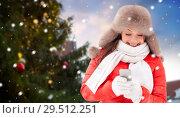 Купить «woman with smartphone over christmas tree», фото № 29512251, снято 7 января 2017 г. (c) Syda Productions / Фотобанк Лори