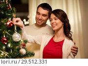 Купить «happy couple decorating christmas tree at home», фото № 29512331, снято 11 января 2018 г. (c) Syda Productions / Фотобанк Лори