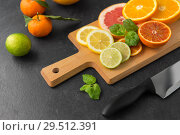 Купить «close up of fruits and knife on slate table top», фото № 29512391, снято 4 апреля 2018 г. (c) Syda Productions / Фотобанк Лори