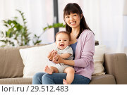 Купить «happy young asian mother with little baby at home», фото № 29512483, снято 5 мая 2018 г. (c) Syda Productions / Фотобанк Лори