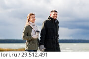 Купить «couple with tumbler walking along autumn beach», фото № 29512491, снято 29 сентября 2018 г. (c) Syda Productions / Фотобанк Лори