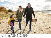 Купить «happy family going to picnic on beach in autumn», фото № 29512499, снято 29 сентября 2018 г. (c) Syda Productions / Фотобанк Лори
