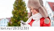 Купить «woman with smartphone over christmas tree», фото № 29512551, снято 7 января 2017 г. (c) Syda Productions / Фотобанк Лори