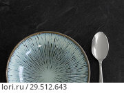 Купить «close up of ceramic plate and spoon on table», фото № 29512643, снято 4 апреля 2018 г. (c) Syda Productions / Фотобанк Лори